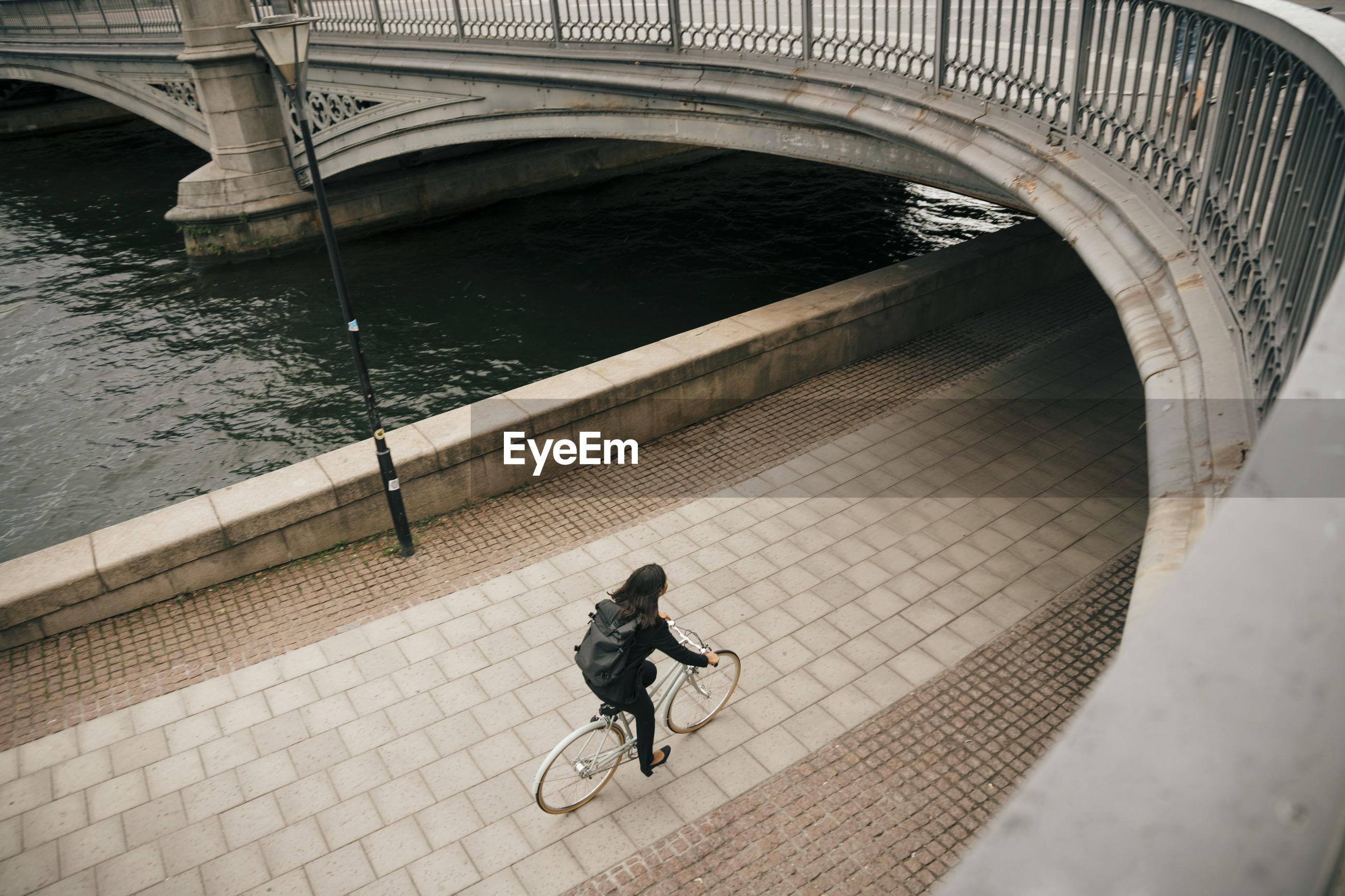 HIGH ANGLE VIEW OF WOMAN RIDING BICYCLE AT BRIDGE