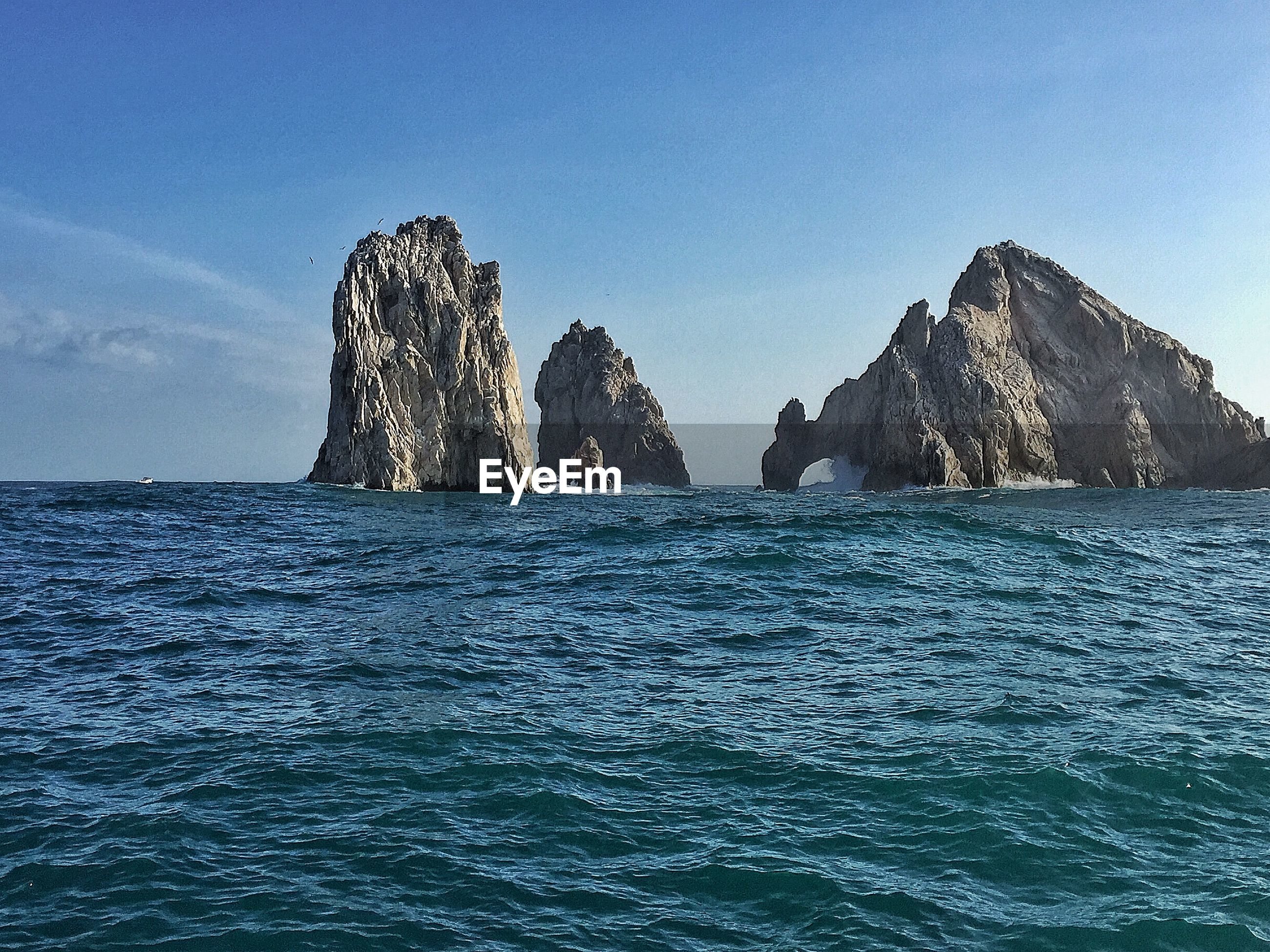 Rock formation in front of sea against sky on sunny day