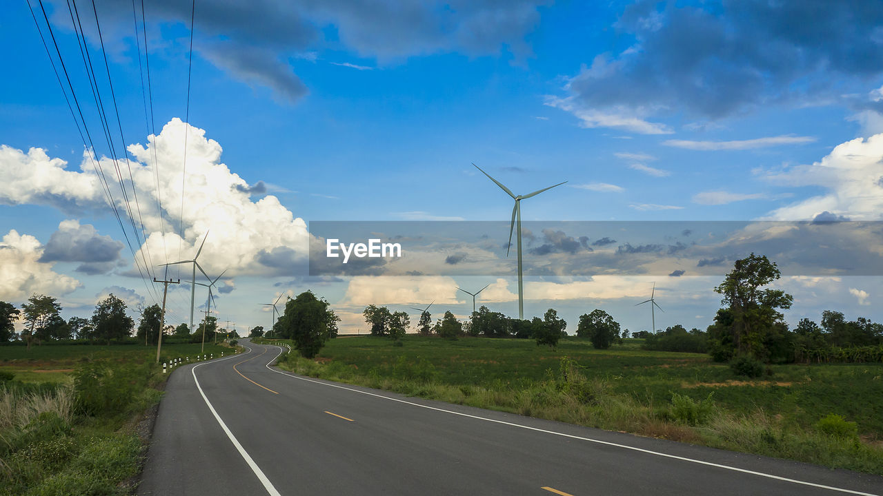 road, sky, transportation, cloud - sky, environment, fuel and power generation, the way forward, plant, nature, direction, landscape, wind turbine, road marking, turbine, marking, tree, environmental conservation, symbol, no people, sign, diminishing perspective, outdoors, electricity