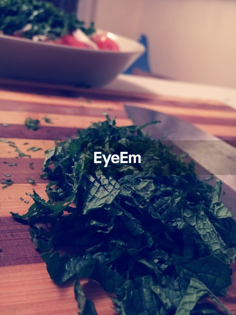 Close-up of chopped mint leaves on cutting board in kitchen