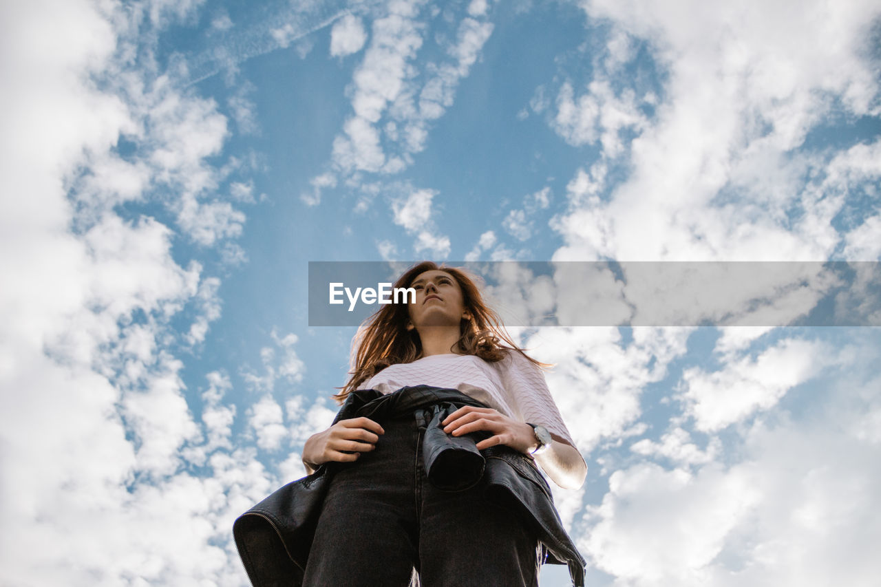 Low Angle View Of Young Woman Standing Against Cloudy Sky