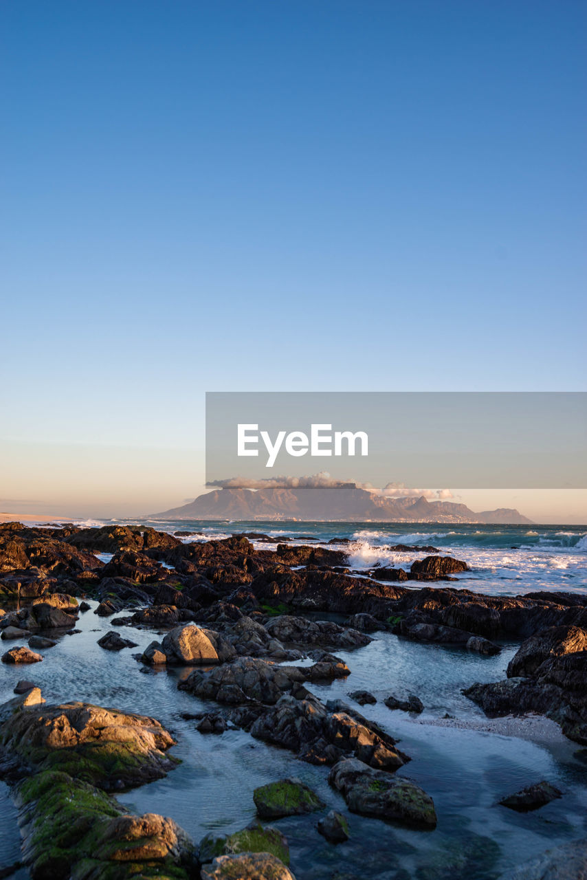 sky, scenics - nature, beauty in nature, copy space, water, tranquil scene, tranquility, clear sky, sunset, nature, no people, sea, rock, solid, rock - object, land, blue, non-urban scene, beach, outdoors, rocky coastline