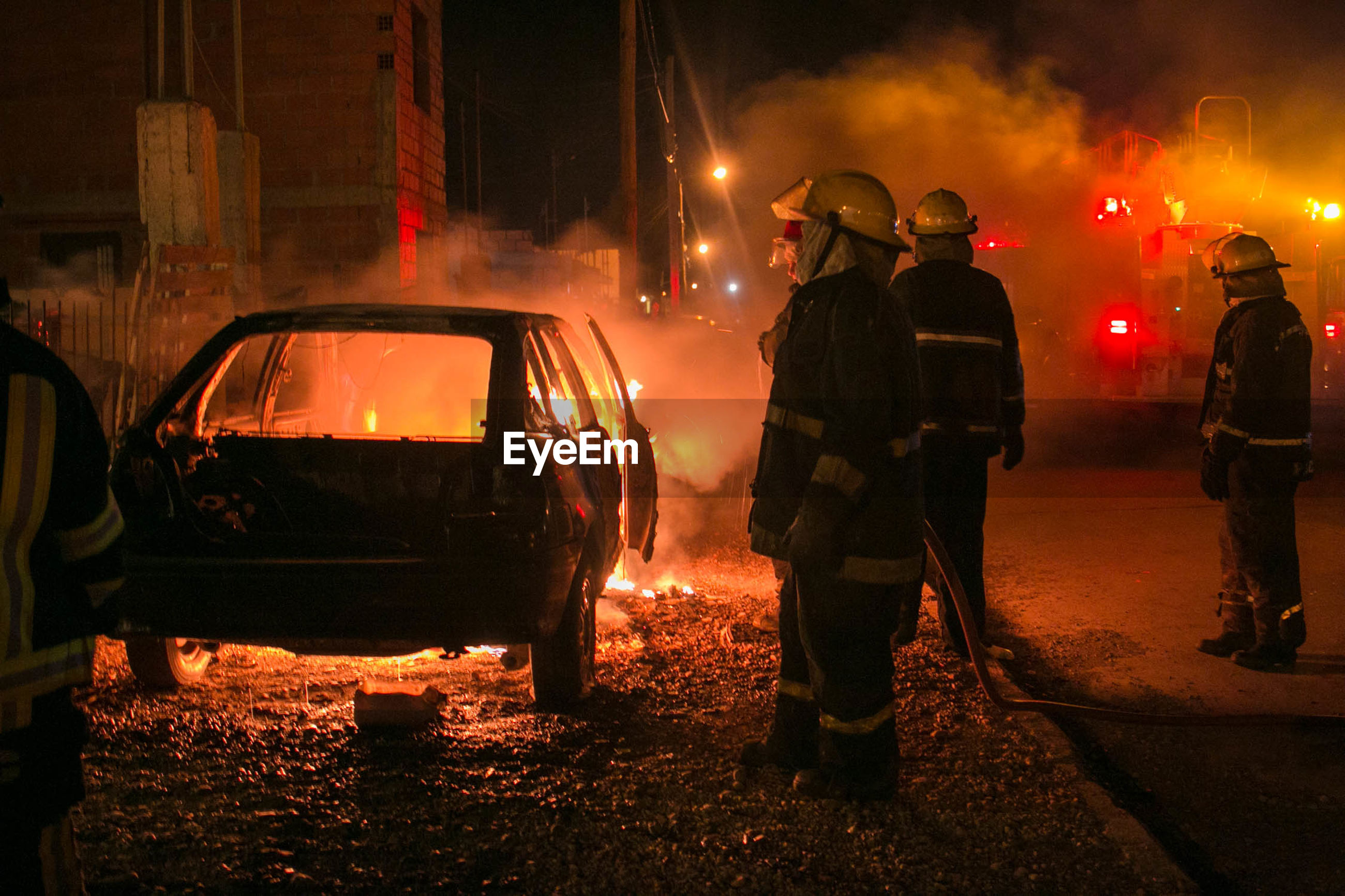 Firefighters standing by burning car at night