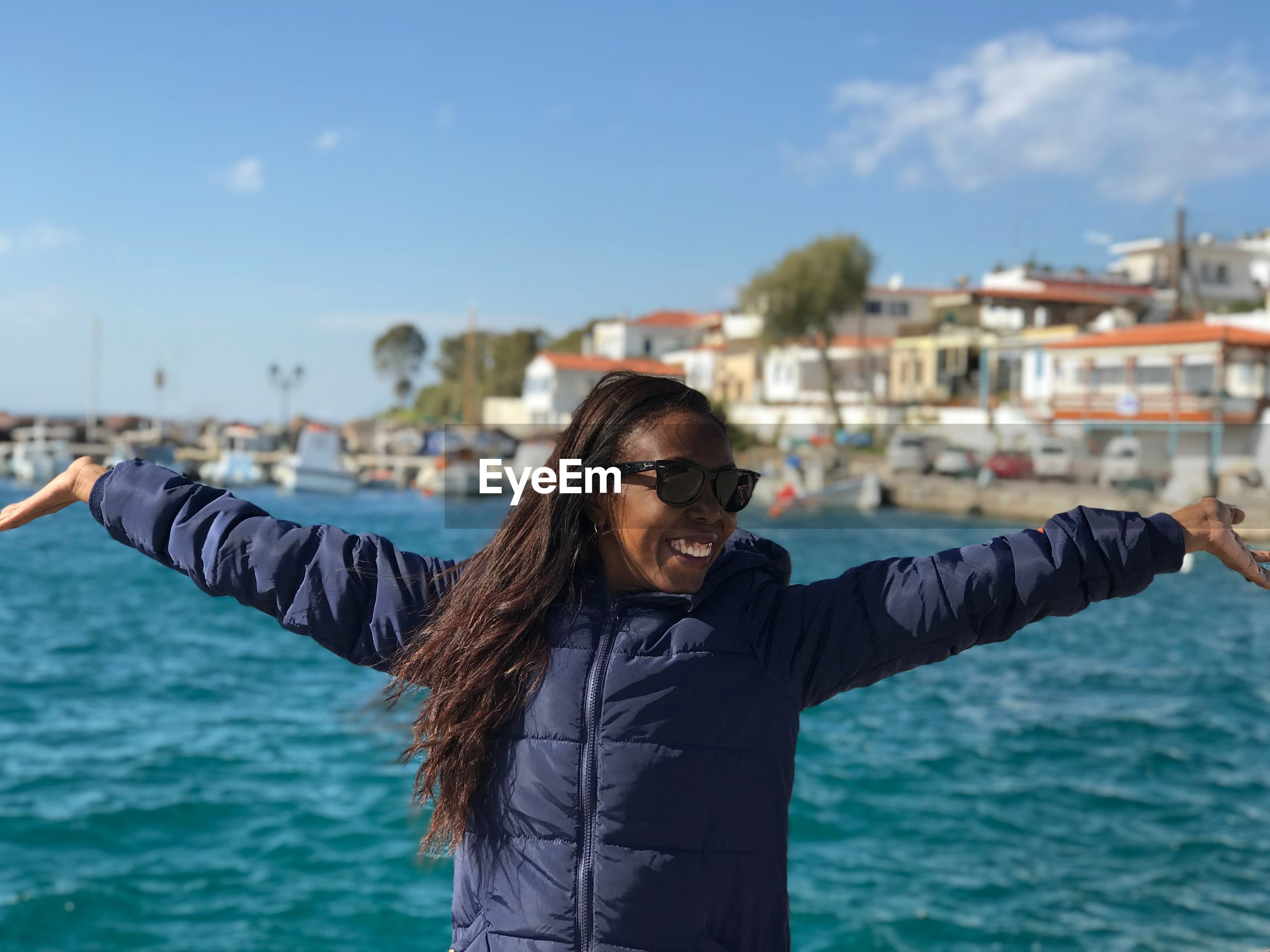 Happy woman standing with arms outstretched against sea in city