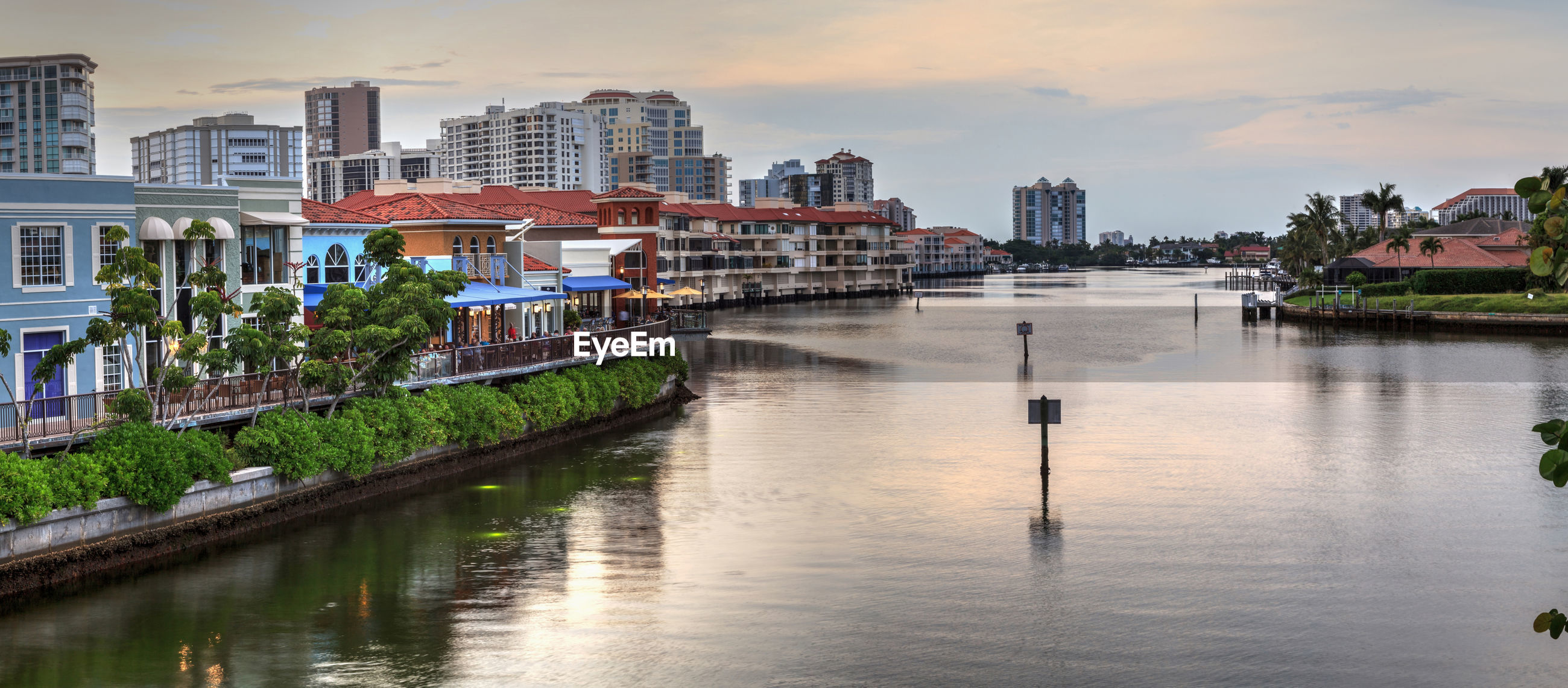 SCENIC VIEW OF RIVER BY BUILDINGS AGAINST SKY IN CITY