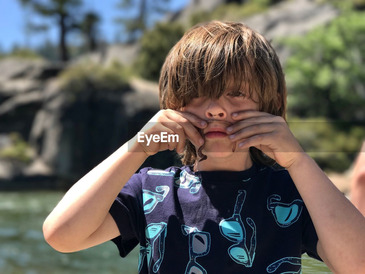 Boy holding worm around mouth as mustache