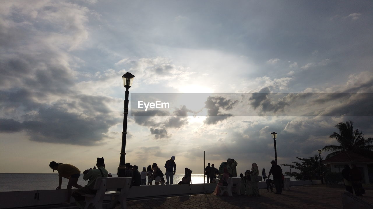 sky, cloud - sky, group of people, street light, street, real people, nature, lifestyles, men, sunset, women, people, leisure activity, outdoors, lighting equipment, silhouette, adult, crowd, beauty in nature