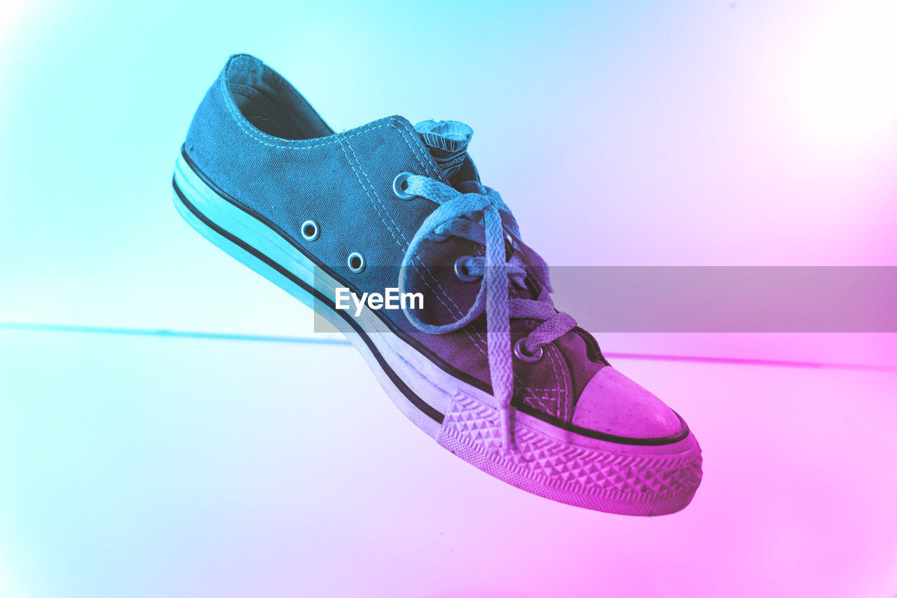 HIGH ANGLE VIEW OF SHOES ON BLUE METAL