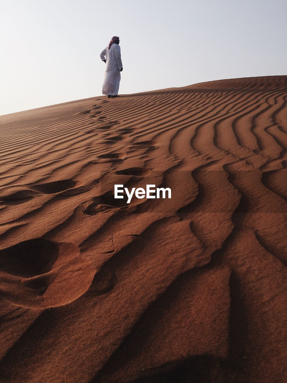 Rear view of man standing on sand at desert against sky
