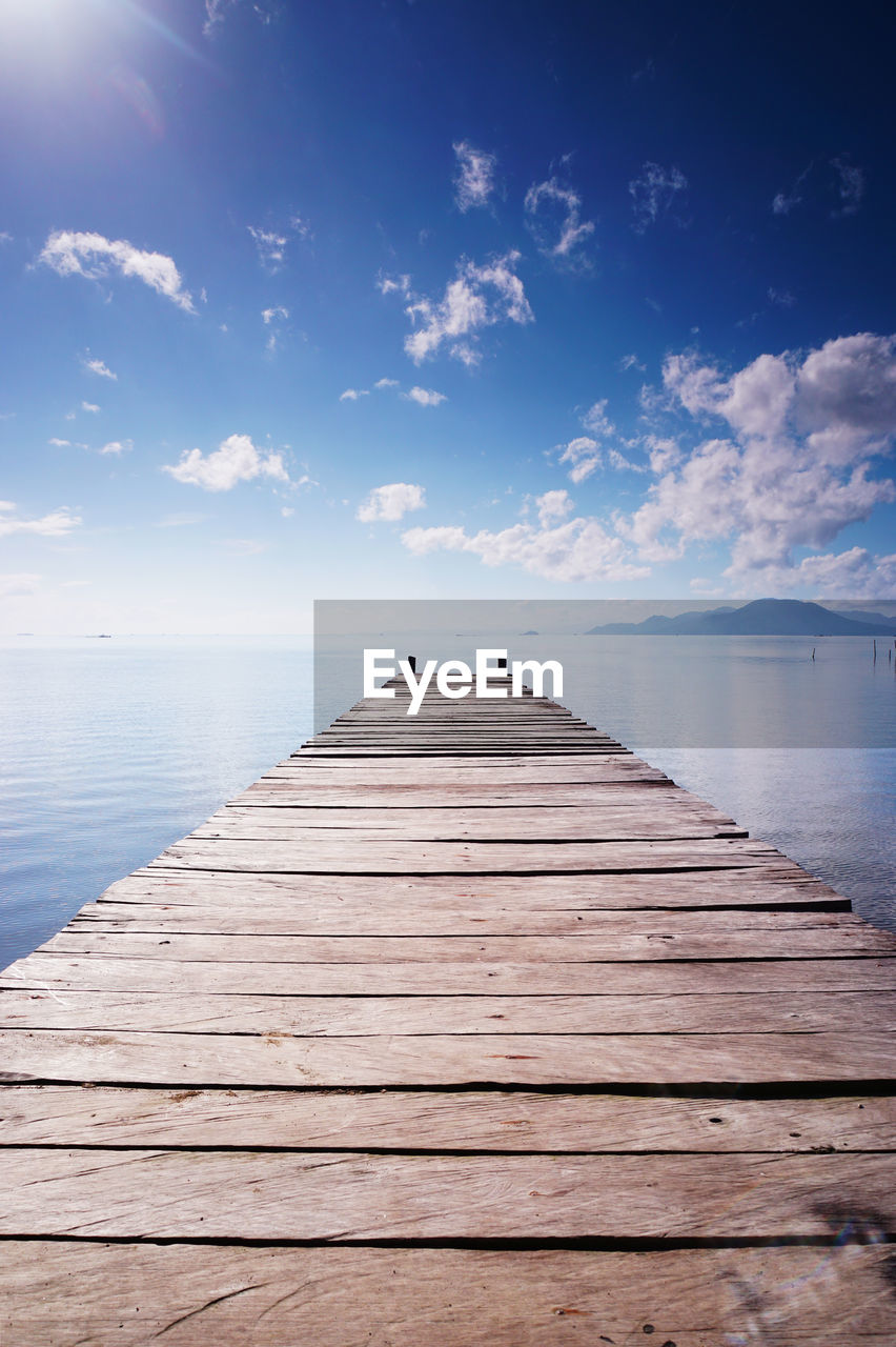sky, wood - material, water, the way forward, sea, pier, direction, tranquil scene, tranquility, cloud - sky, beauty in nature, horizon over water, scenics - nature, horizon, jetty, nature, idyllic, diminishing perspective, no people, wood paneling, wood, outdoors, long