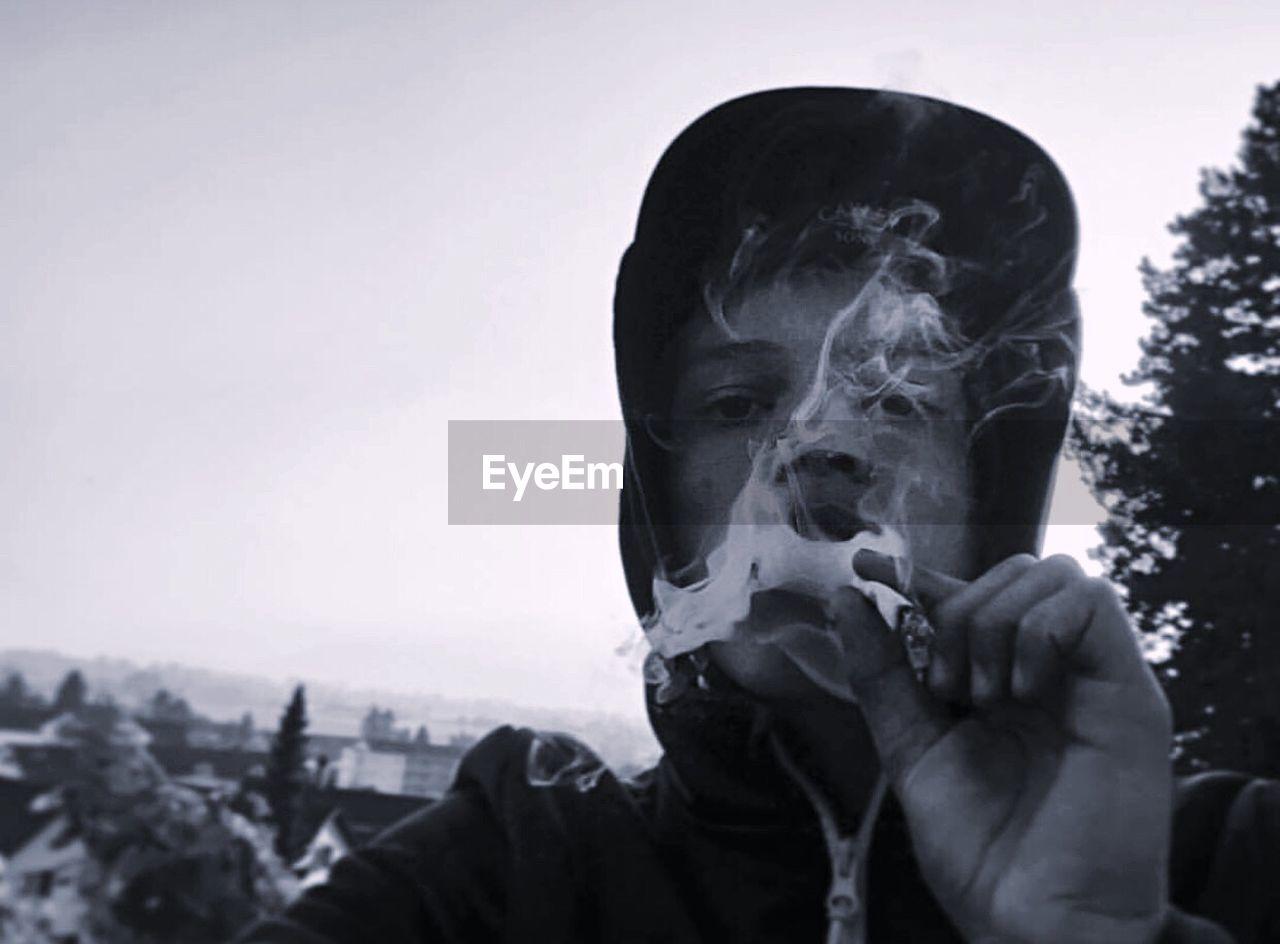 Portrait Of Man Smoking Marijuana Joint Against Sky