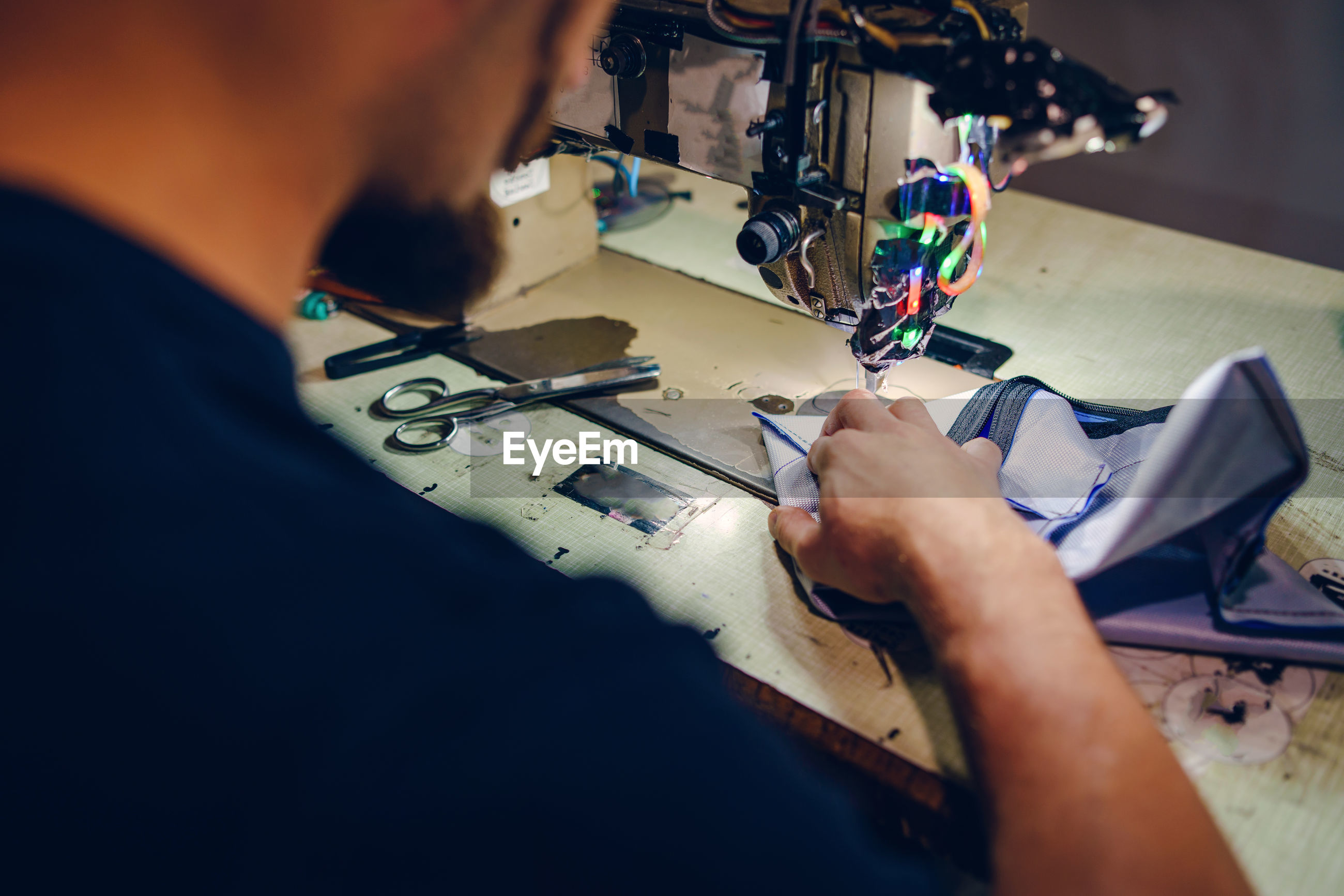 High angle view of man working on sewing machine