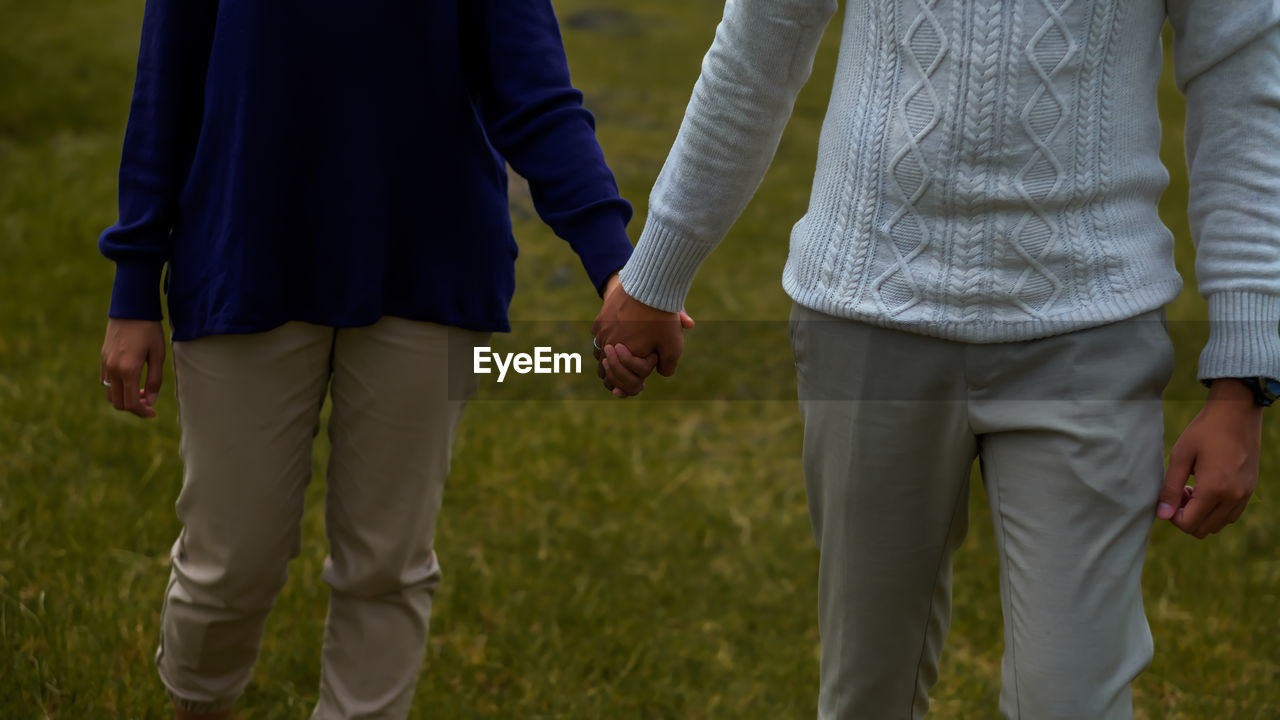real people, love, two people, men, togetherness, positive emotion, bonding, emotion, land, people, field, holding hands, leisure activity, women, midsection, rear view, couple - relationship, standing, grass, focus on foreground, hand, outdoors