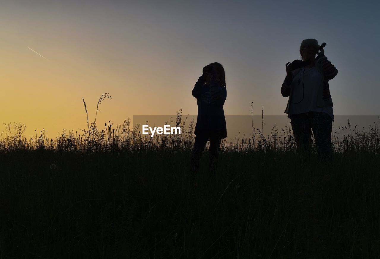 Woman With Daughter Standing On Grassy Field Against Sky During Sunset