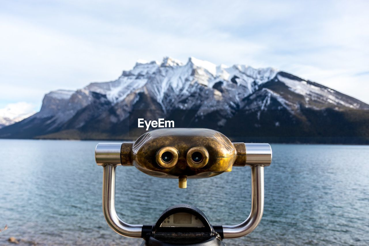Close-Up Of Coin-Operated Binoculars By Lake Against Mountain