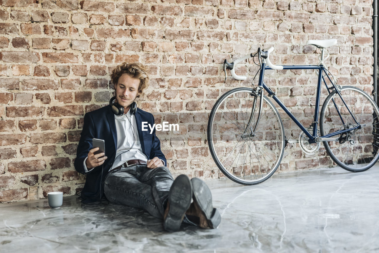 YOUNG MAN SITTING ON WALL WITH BICYCLE AND PEOPLE