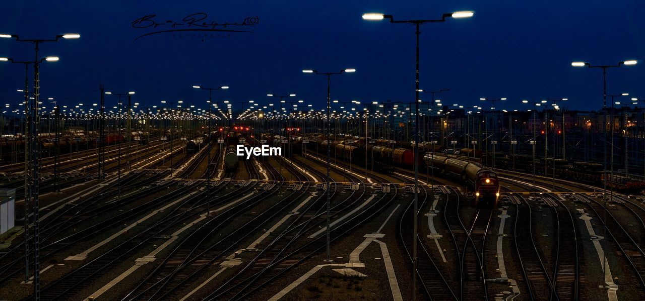 HIGH ANGLE VIEW OF RAILROAD TRACKS AT NIGHT