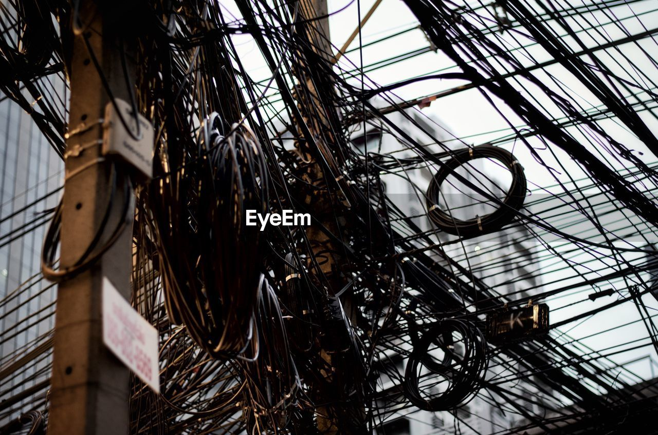 low angle view, built structure, architecture, metal, no people, day, outdoors, nature, selective focus, building exterior, complexity, abandoned, sky, industry, run-down, close-up, decline, building, tangled, deterioration, power supply, ruined