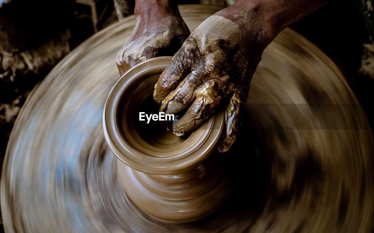 human hand, hand, spinning, motion, craft, art and craft, skill, pottery, real people, making, working, human body part, molding a shape, creativity, clay, expertise, indoors, one person, craftsperson, unrecognizable person, body part, preparation, finger, mud