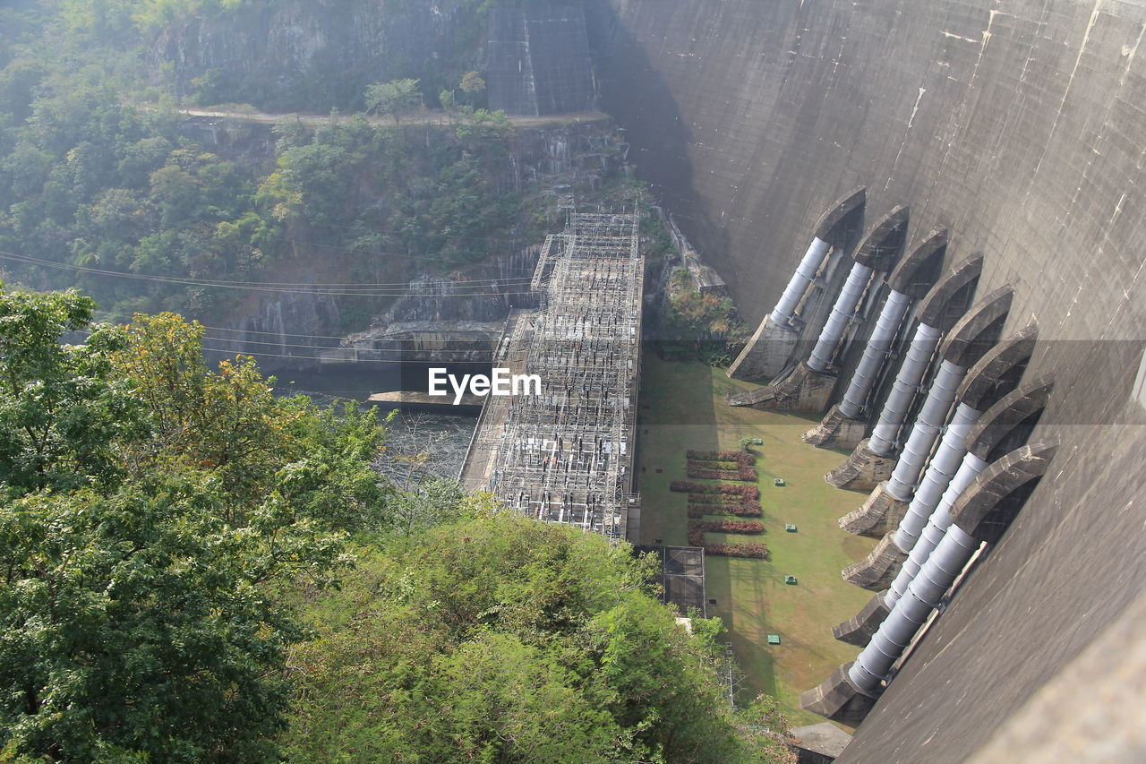tree, plant, architecture, built structure, hydroelectric power, nature, day, high angle view, dam, growth, no people, outdoors, fuel and power generation, building exterior, green color, transportation, water, industry, sunlight, renewable energy