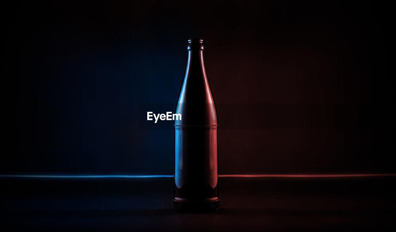 Close-up of illuminated colorful beer bottle against black background