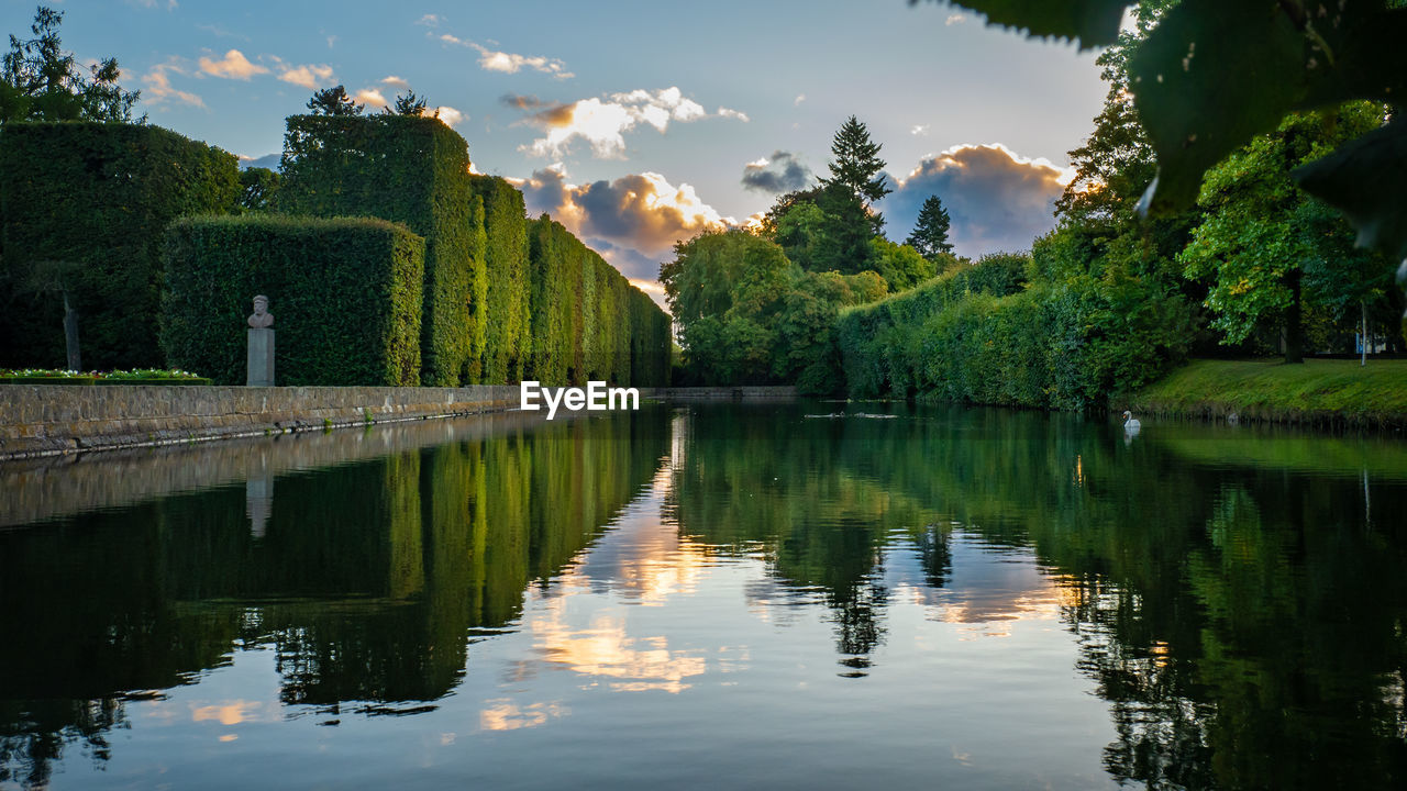 reflection, water, sky, tree, lake, plant, waterfront, tranquility, nature, scenics - nature, beauty in nature, tranquil scene, cloud - sky, green color, no people, growth, day, architecture, non-urban scene, reflection lake
