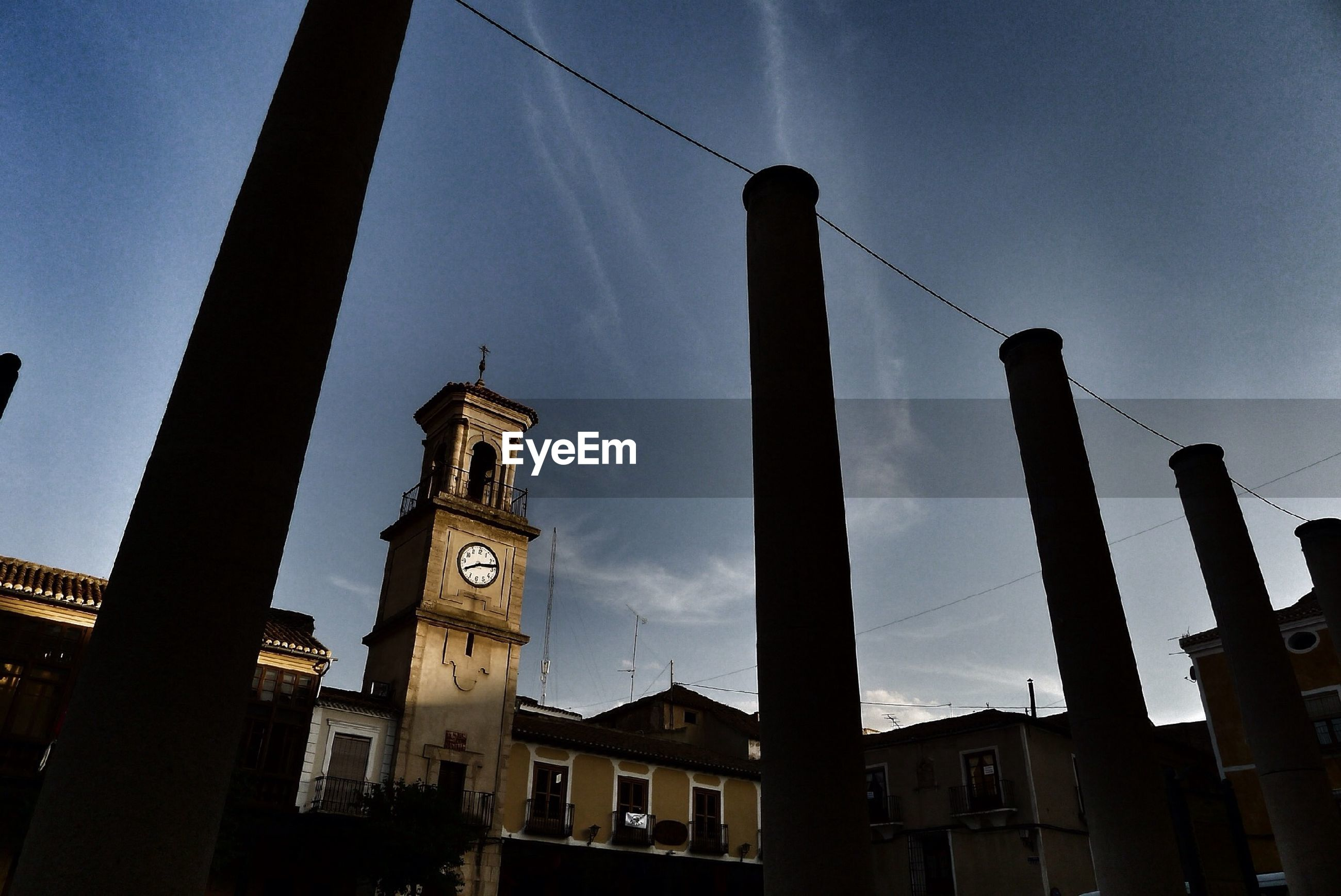 Low angle view of clock tower and silhouette architectural towers against sky