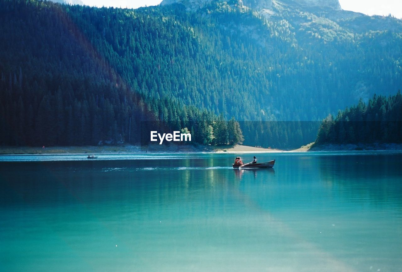 Scenic View Of People In Boat Against Mountains