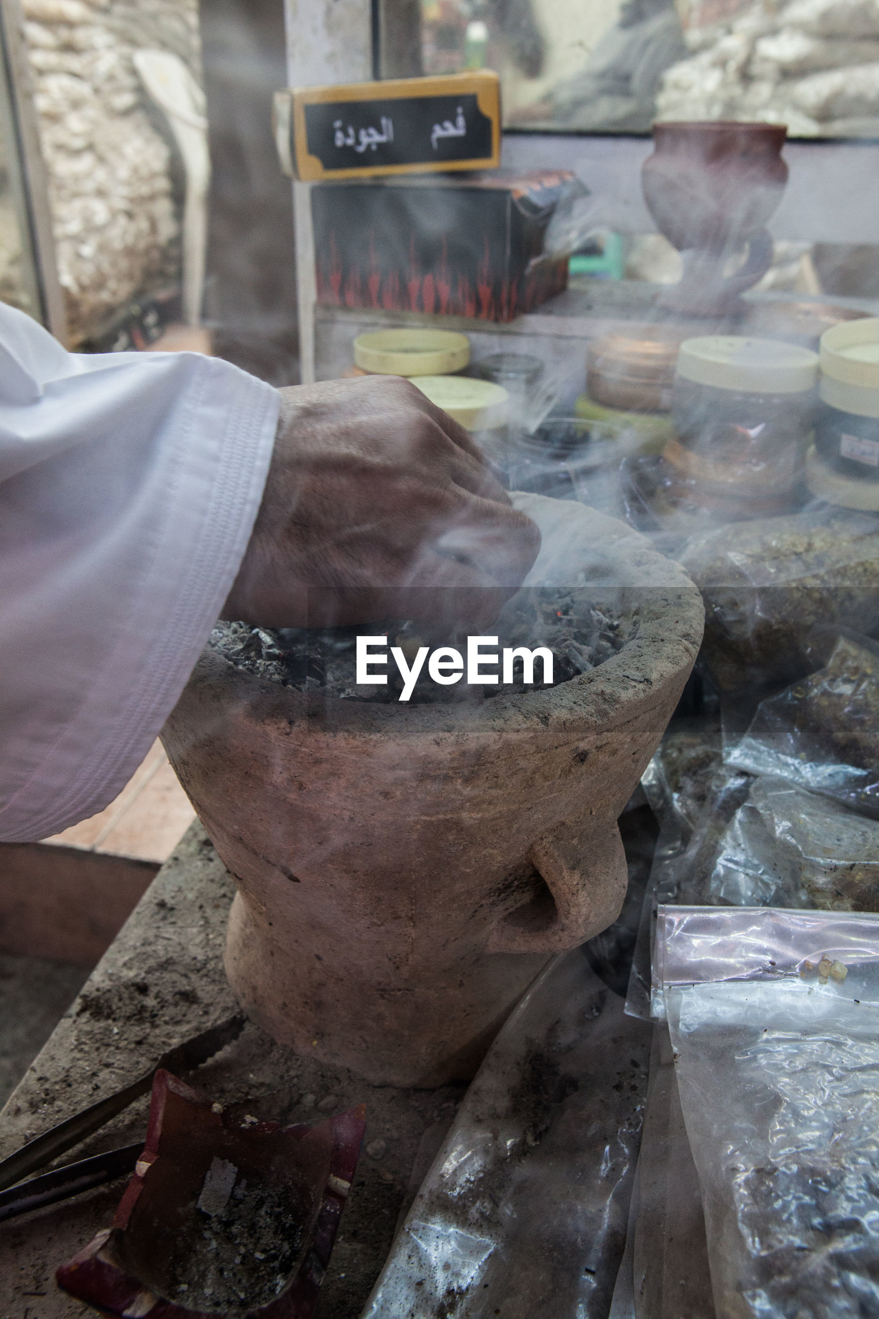 Cropped image of hand burning incense in store
