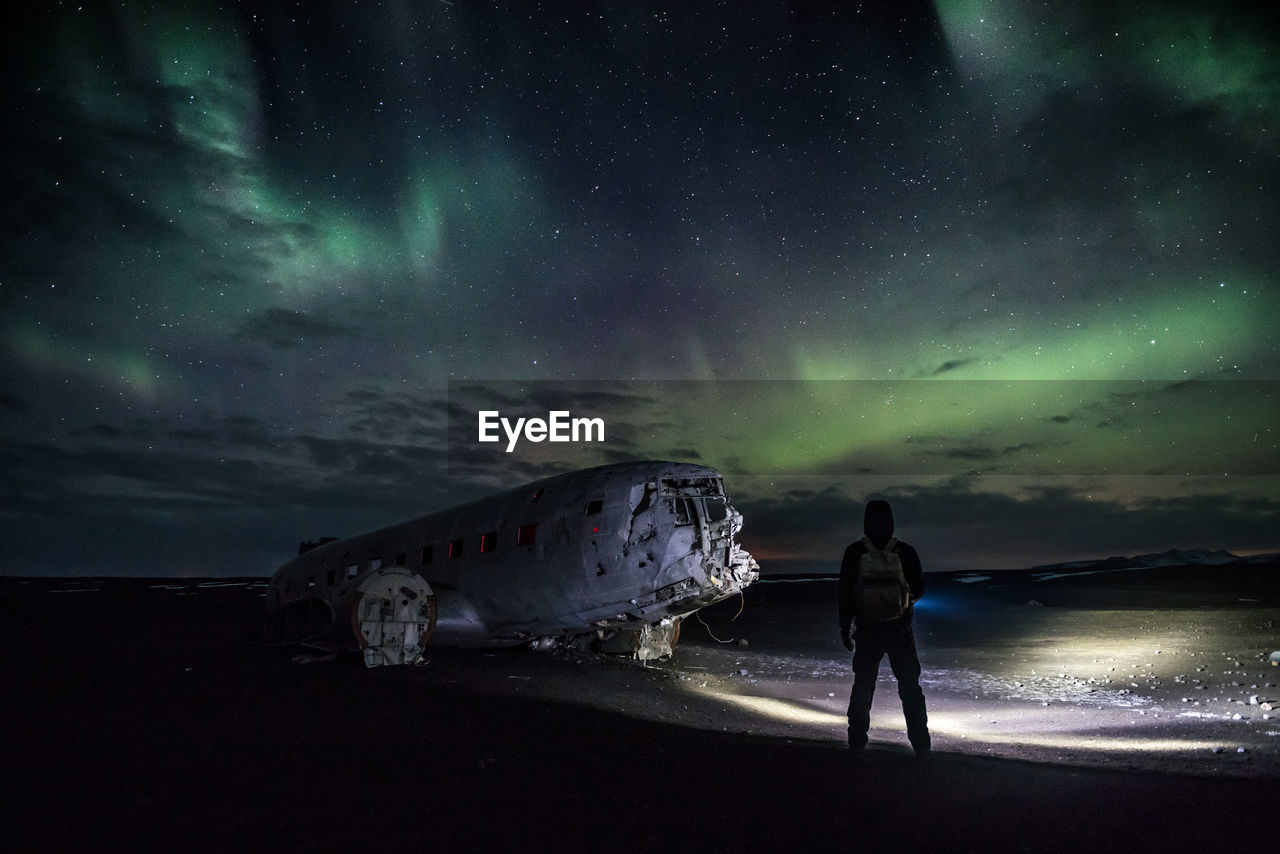 Silhouette Man Looking At Aurora Borealis While Standing By Vehicle