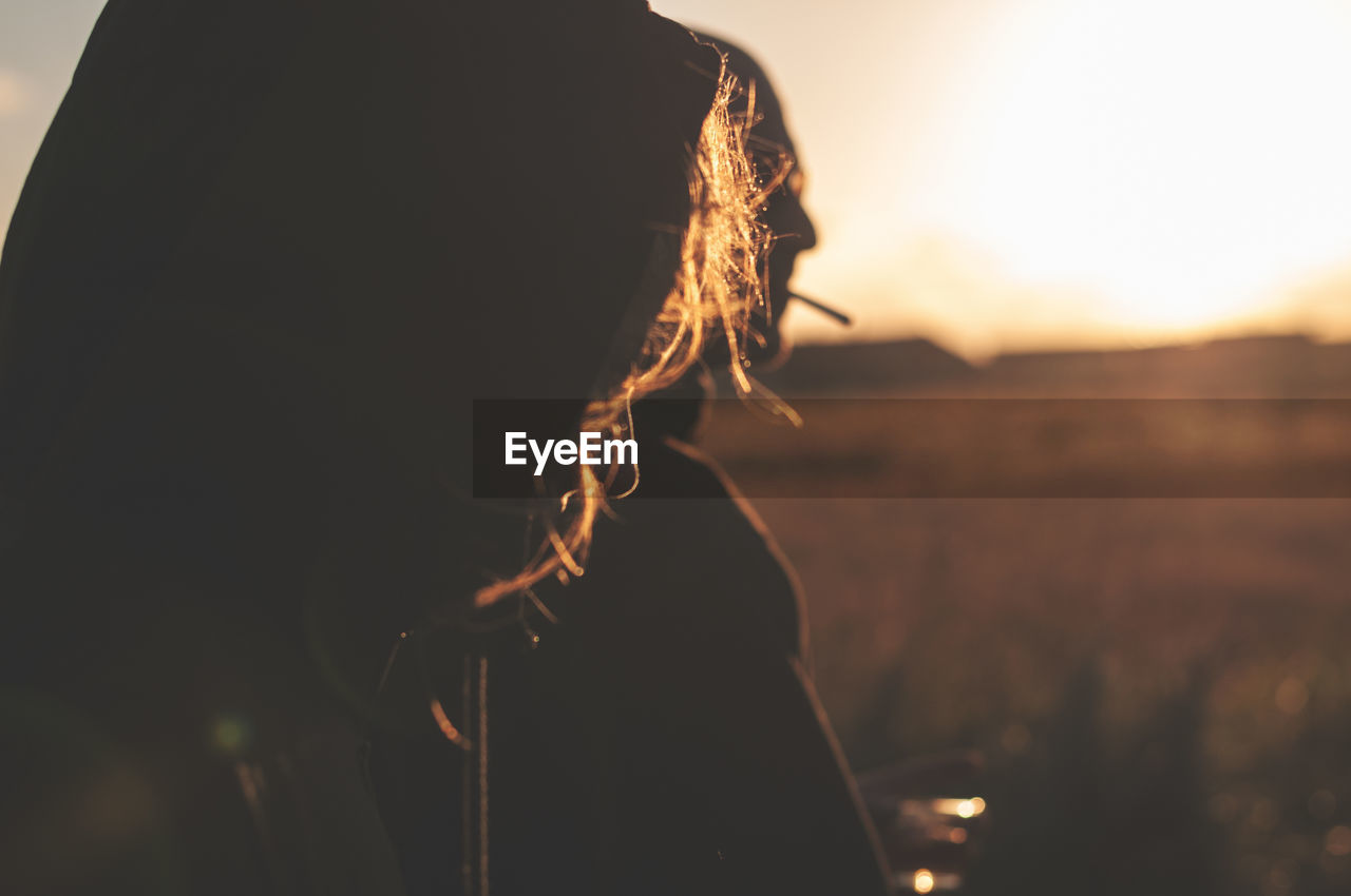 Close-up of woman during sunset