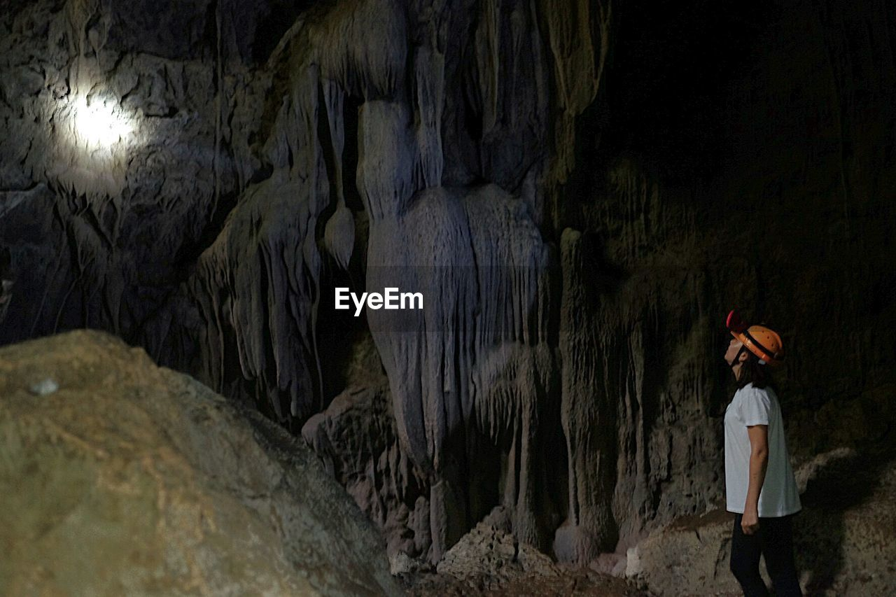 Side View Of Woman Standing In Cave