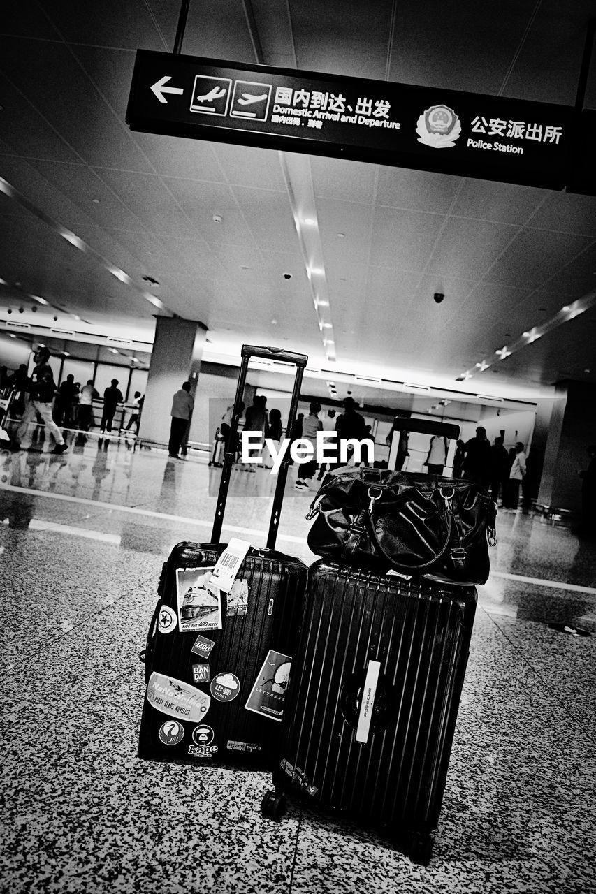 text, travel, group of people, real people, communication, transportation, western script, sign, men, number, people, airport, luggage, public transportation, illuminated, lifestyles, script, journey, incidental people, indoors, waiting, ceiling, station