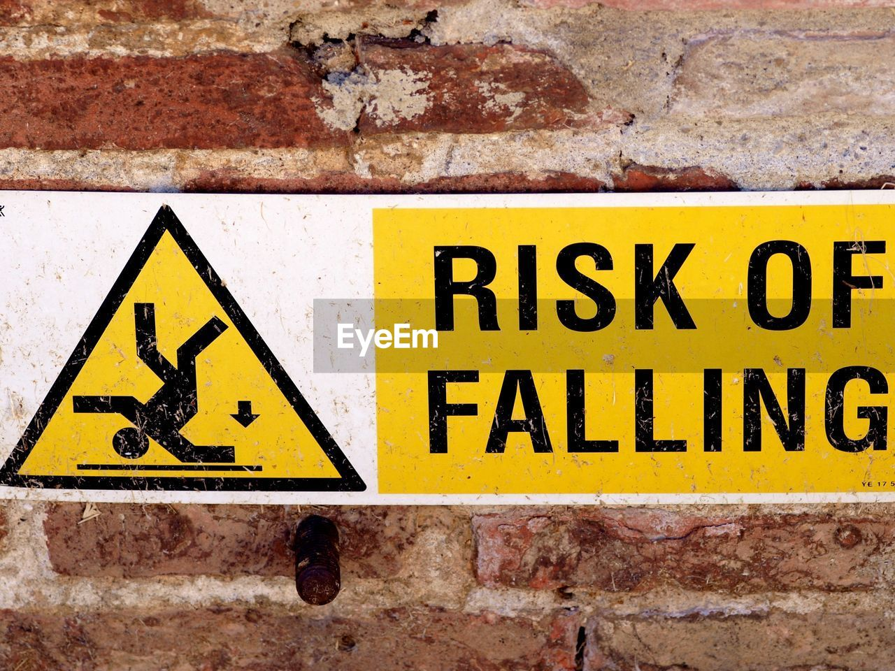 yellow, sign, communication, warning sign, text, wall - building feature, wall, close-up, safety, brick, brick wall, no people, information, information sign, built structure, day, architecture, western script, outdoors, protection, warning symbol
