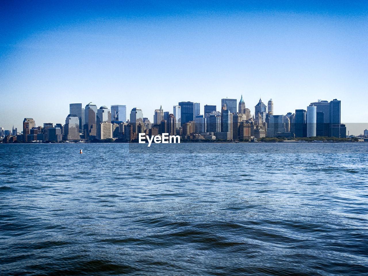 City Skyline By River Against Clear Blue Sky