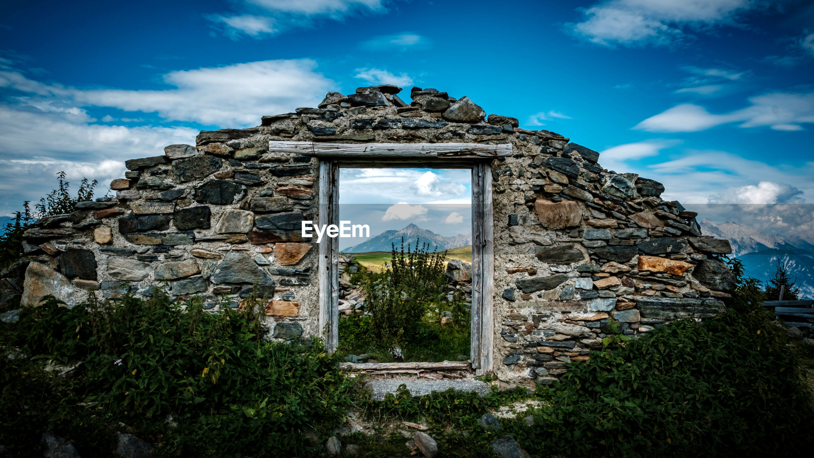 Window on old ruin wall against blue sky