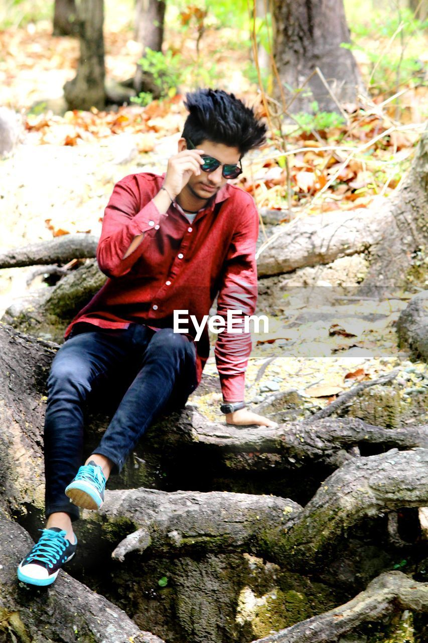Full length of young man sitting on log at forest