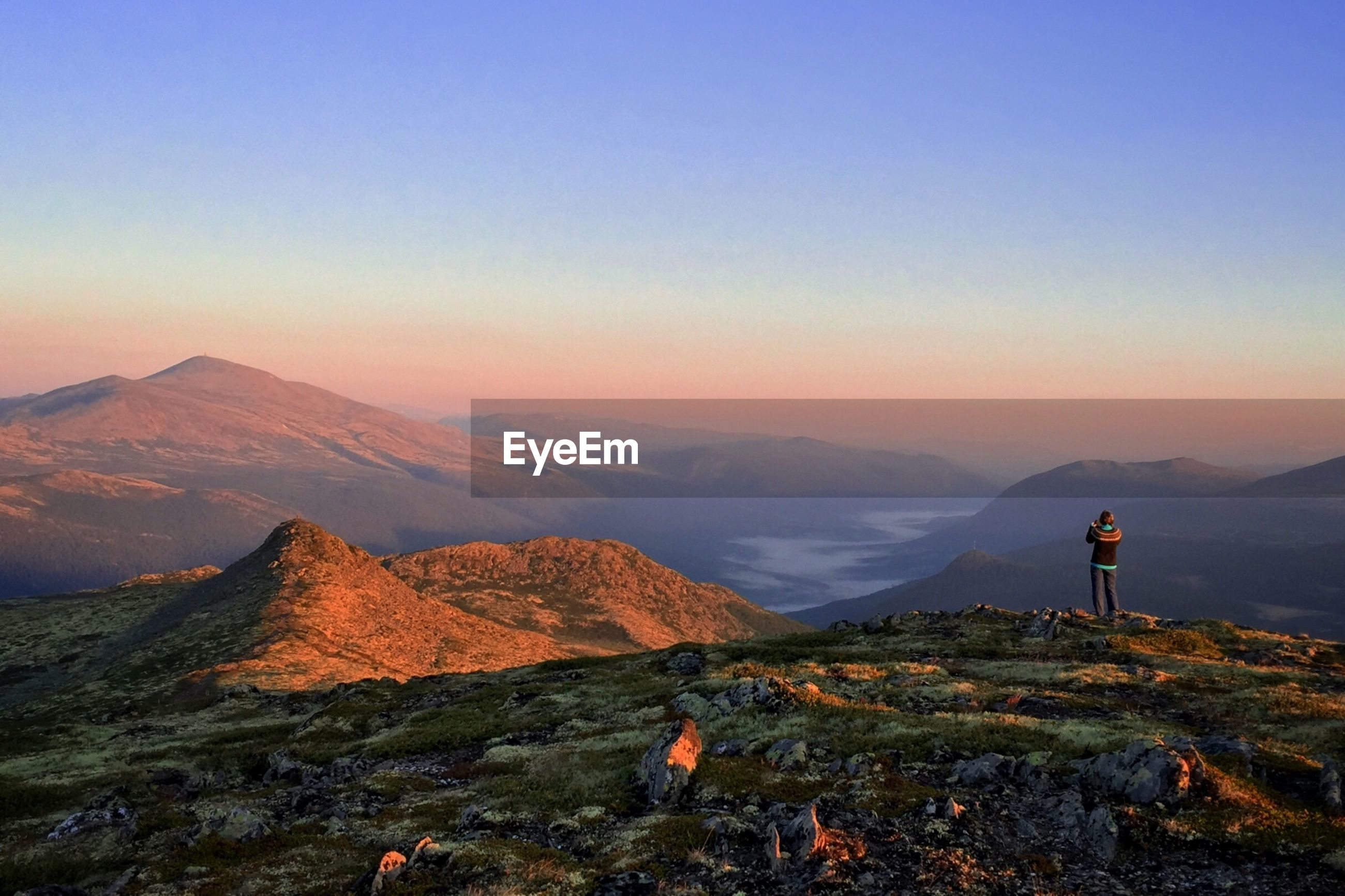 Rear view of woman standing on mountain at sunset