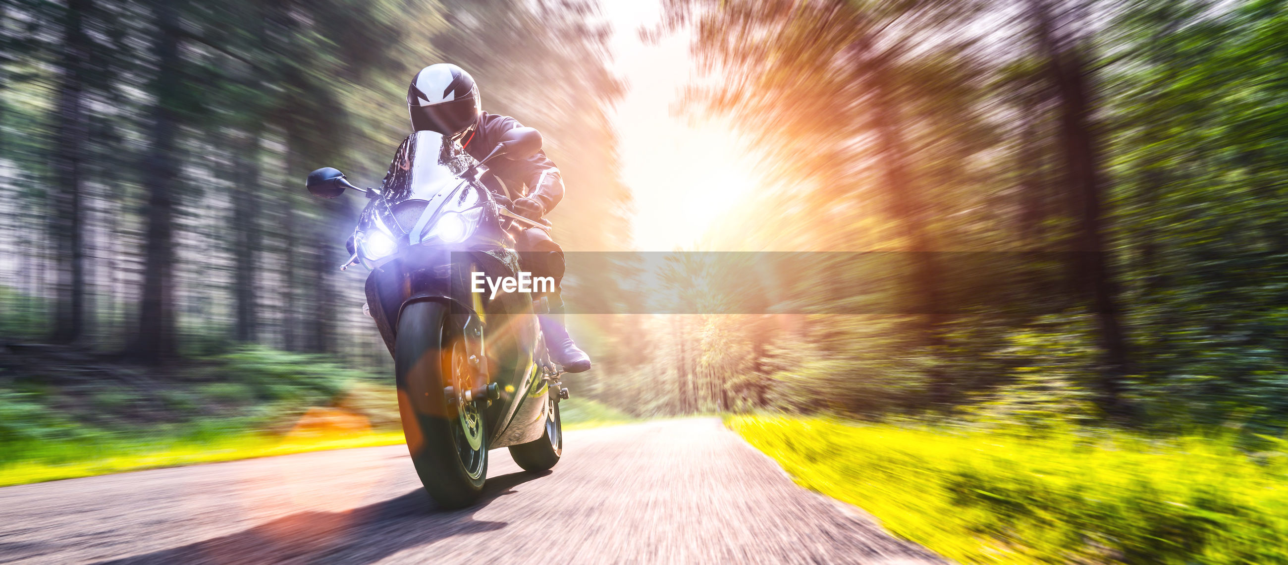 Man riding motorcycle on road in forest