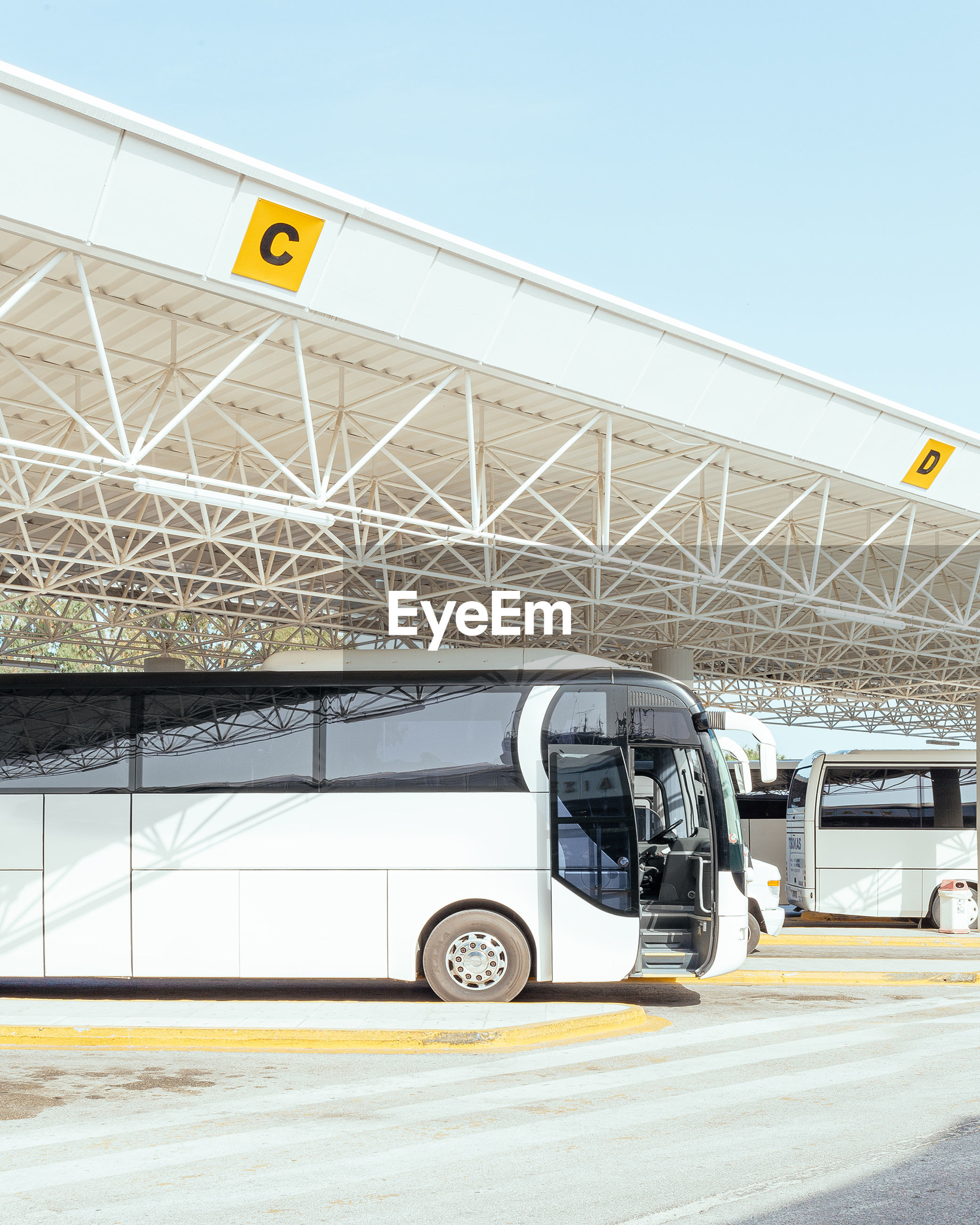 Bus parked by metal structure in city