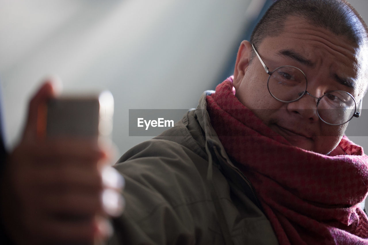 eyeglasses, wireless technology, technology, communication, mobile phone, glasses, smart phone, portrait, headshot, real people, portable information device, lifestyles, leisure activity, connection, one person, activity, front view, telephone, adult, warm clothing