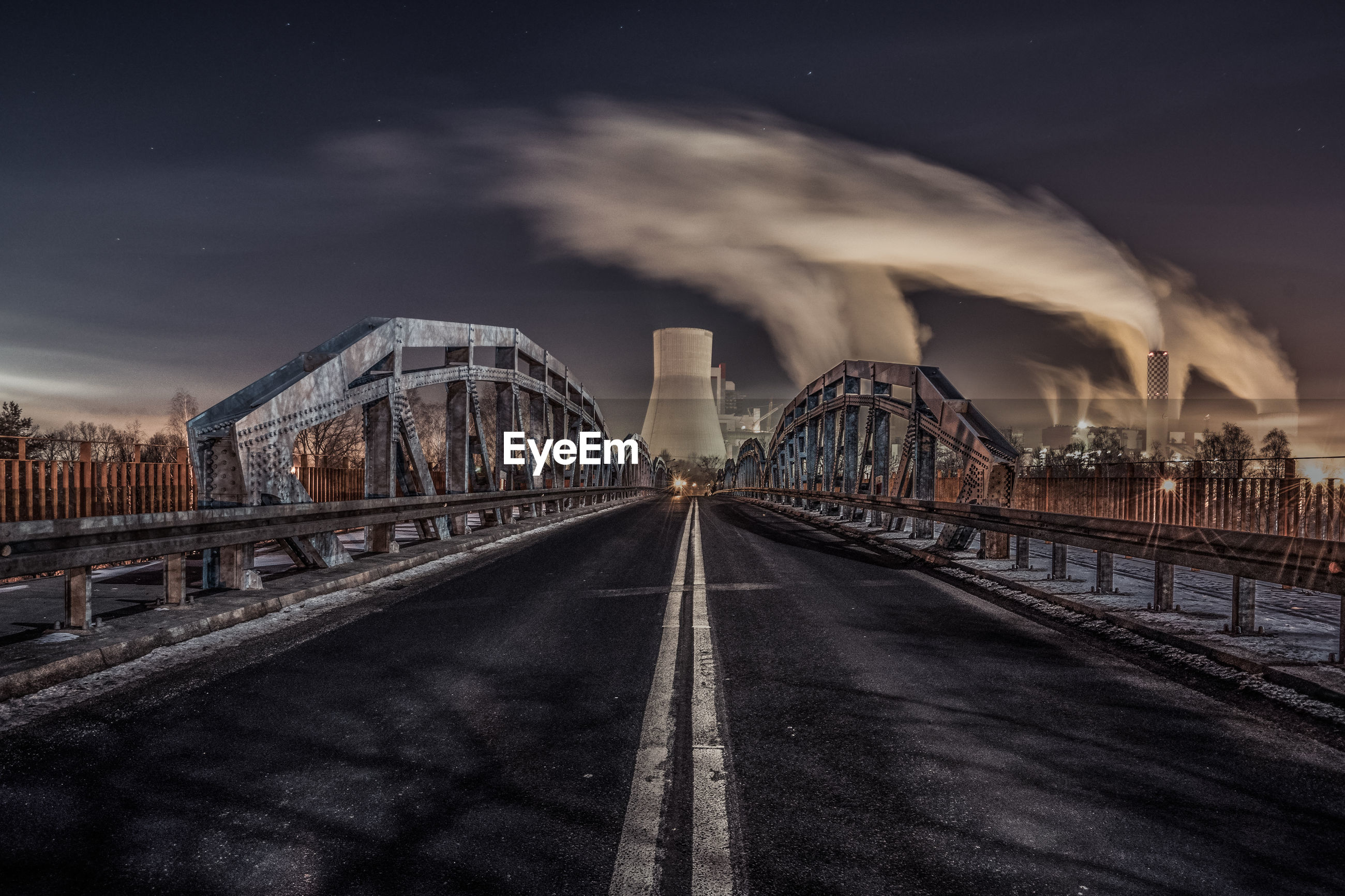View of bridge and factory against sky