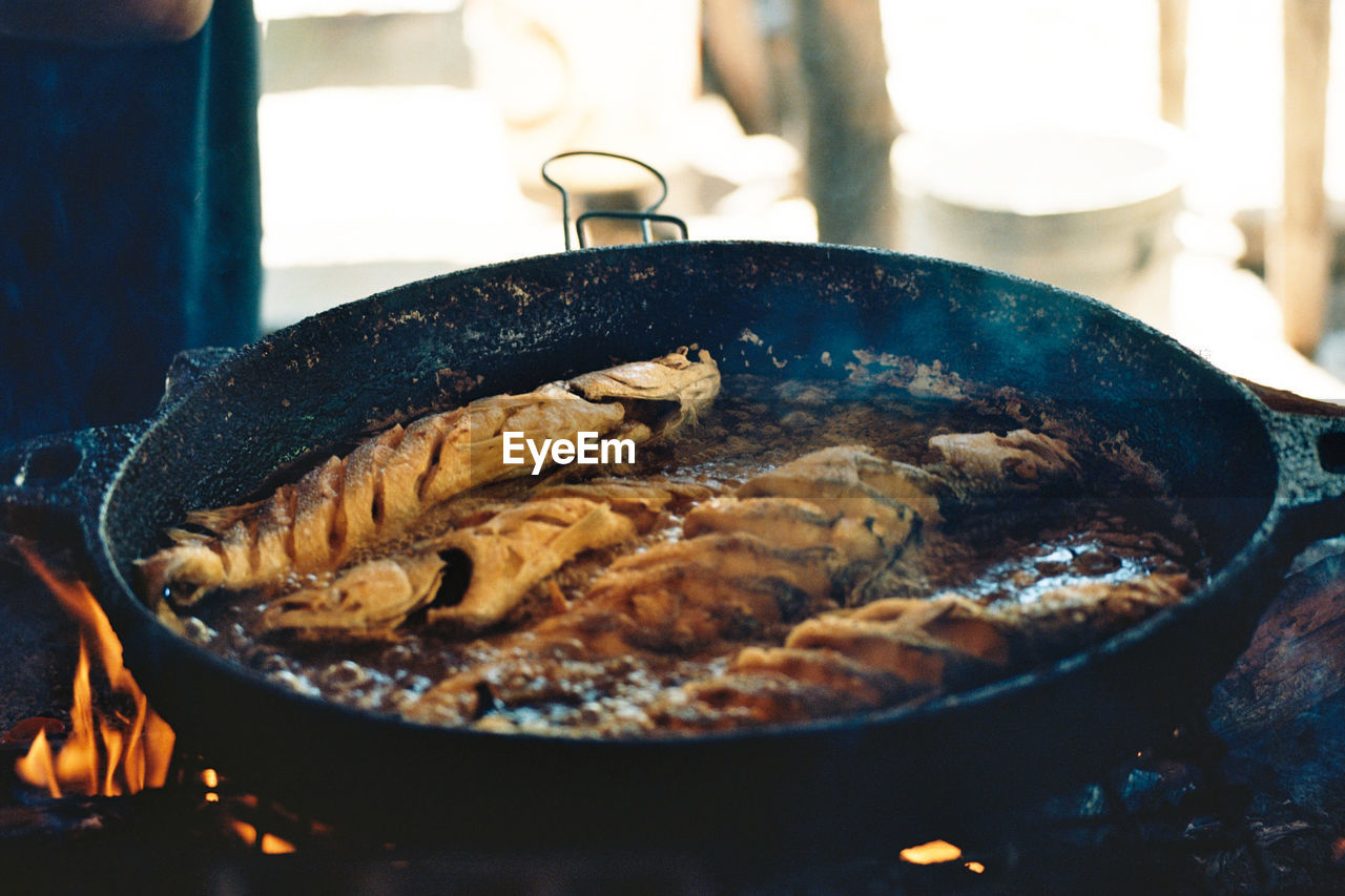 food and drink, food, preparation, freshness, kitchen utensil, indoors, heat - temperature, close-up, no people, burning, household equipment, fire, cooking pan, appliance, still life, pan, fire - natural phenomenon, flame, preparing food, meat