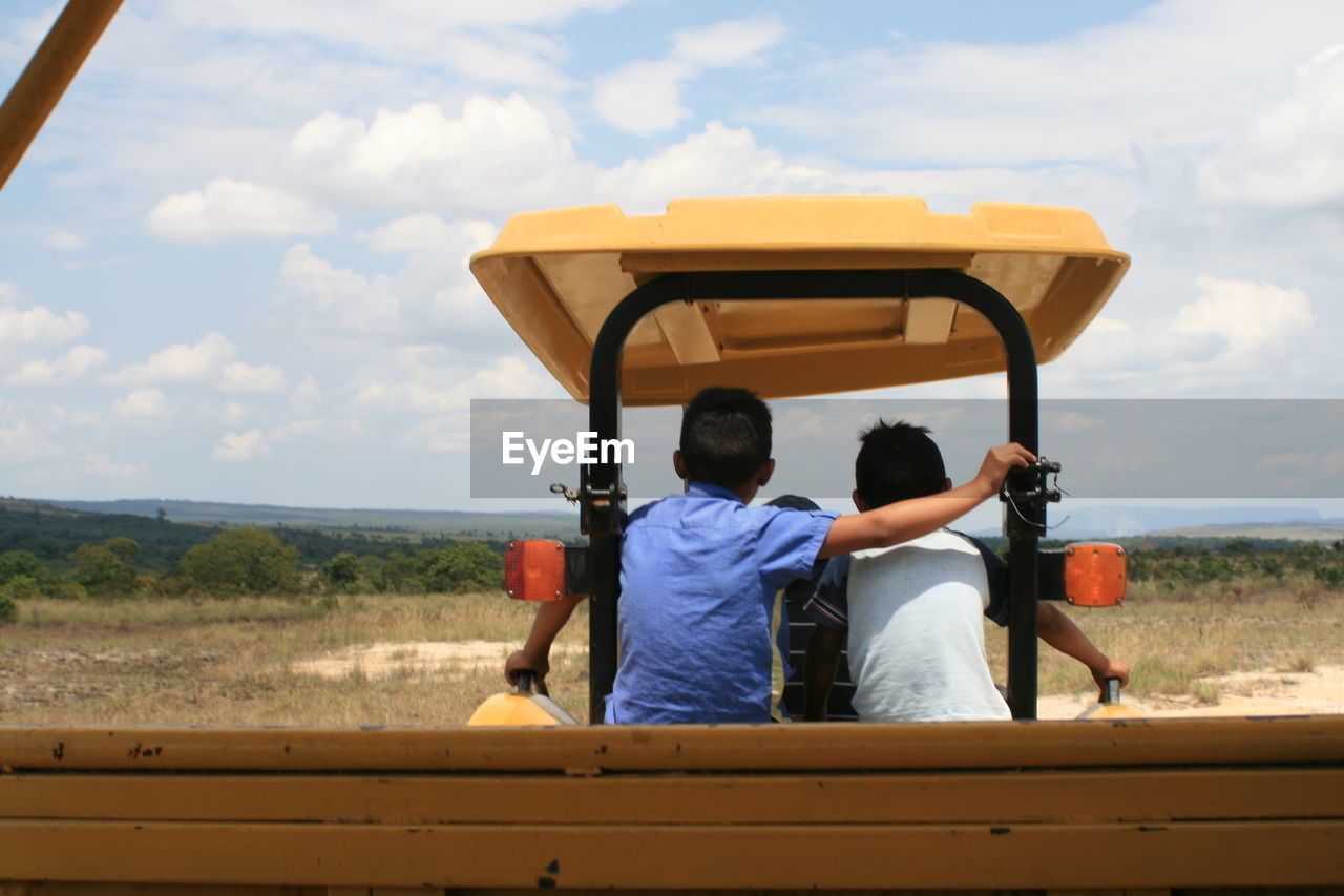 Rear view of boys riding on tractor against cloudy sky