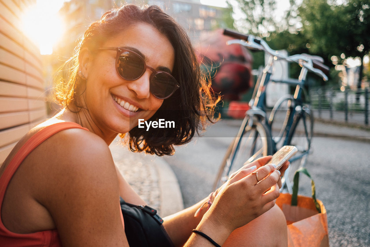 Portrait of smiling woman using mobile phone while sitting outdoors