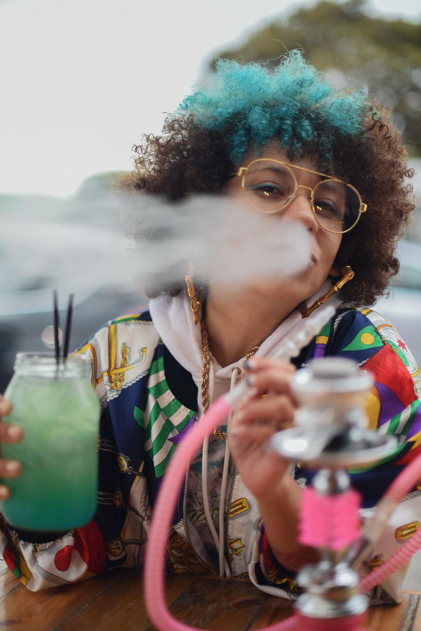 Young Woman Smoking Hookah At Table