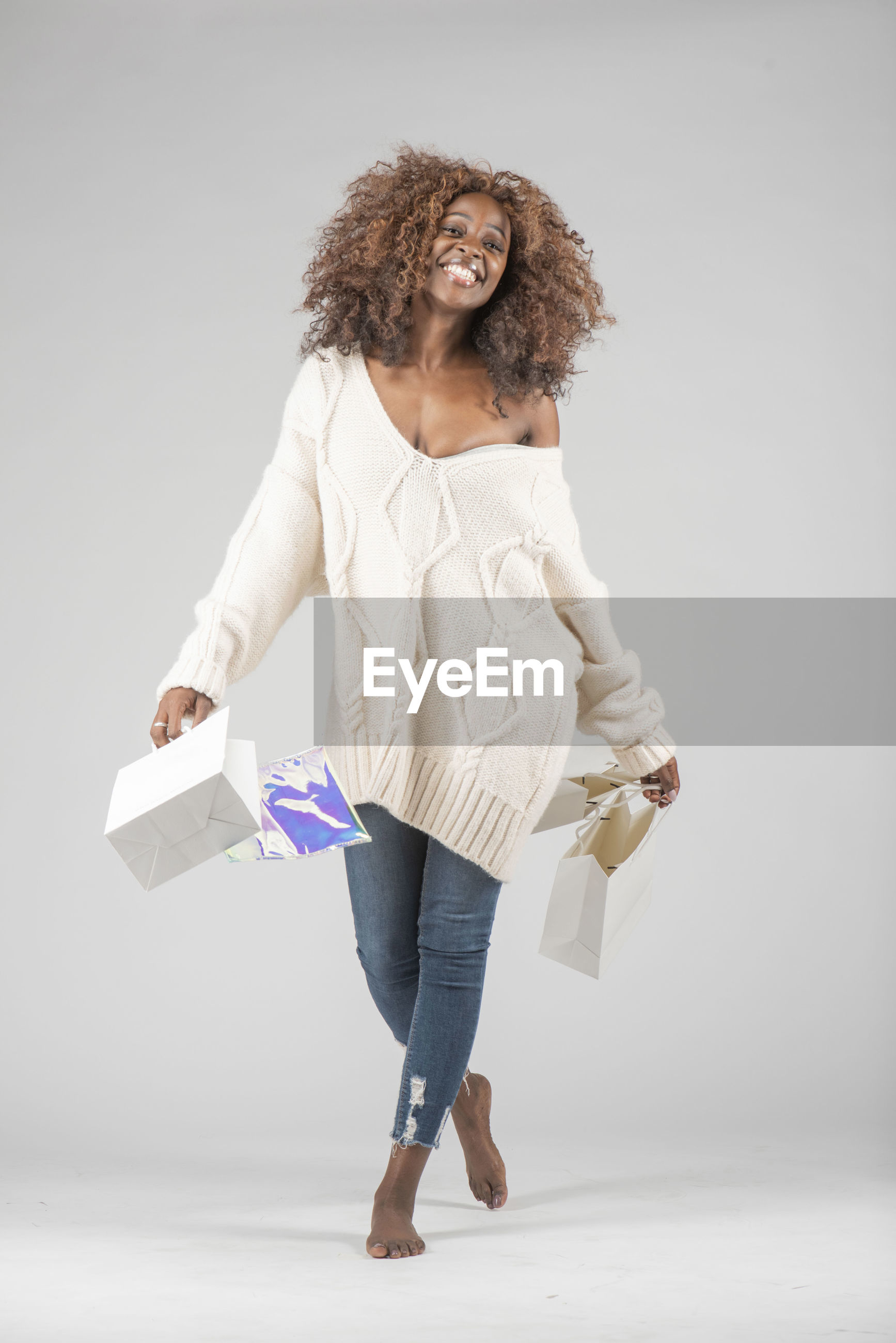 Portrait of happy woman with shopping bags standing against gray background