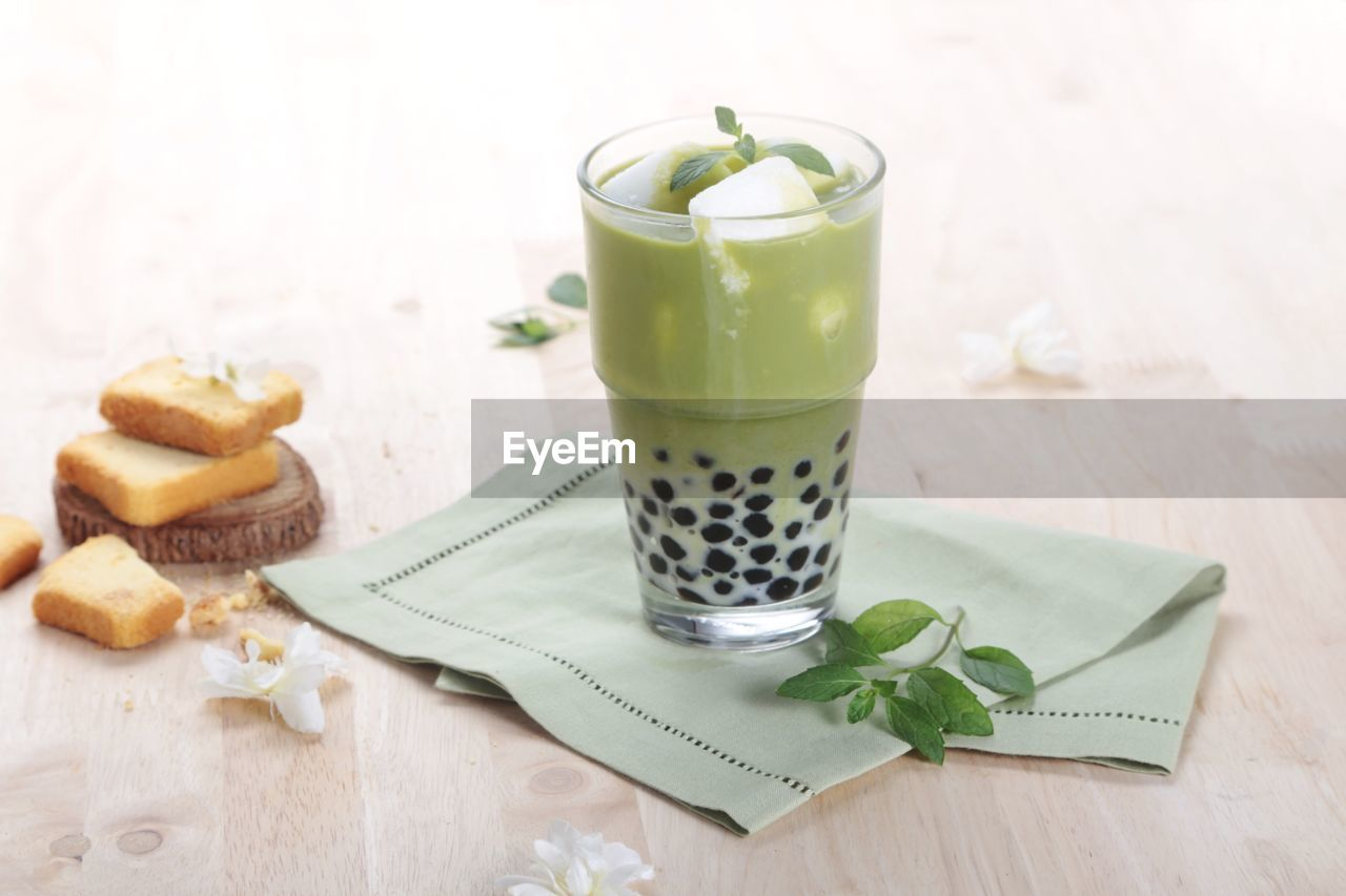 food and drink, food, table, drink, refreshment, glass, freshness, indoors, still life, drinking glass, wood - material, household equipment, no people, high angle view, ready-to-eat, healthy eating, indulgence, eating utensil, leaf, focus on foreground, temptation, mint leaf - culinary, latte