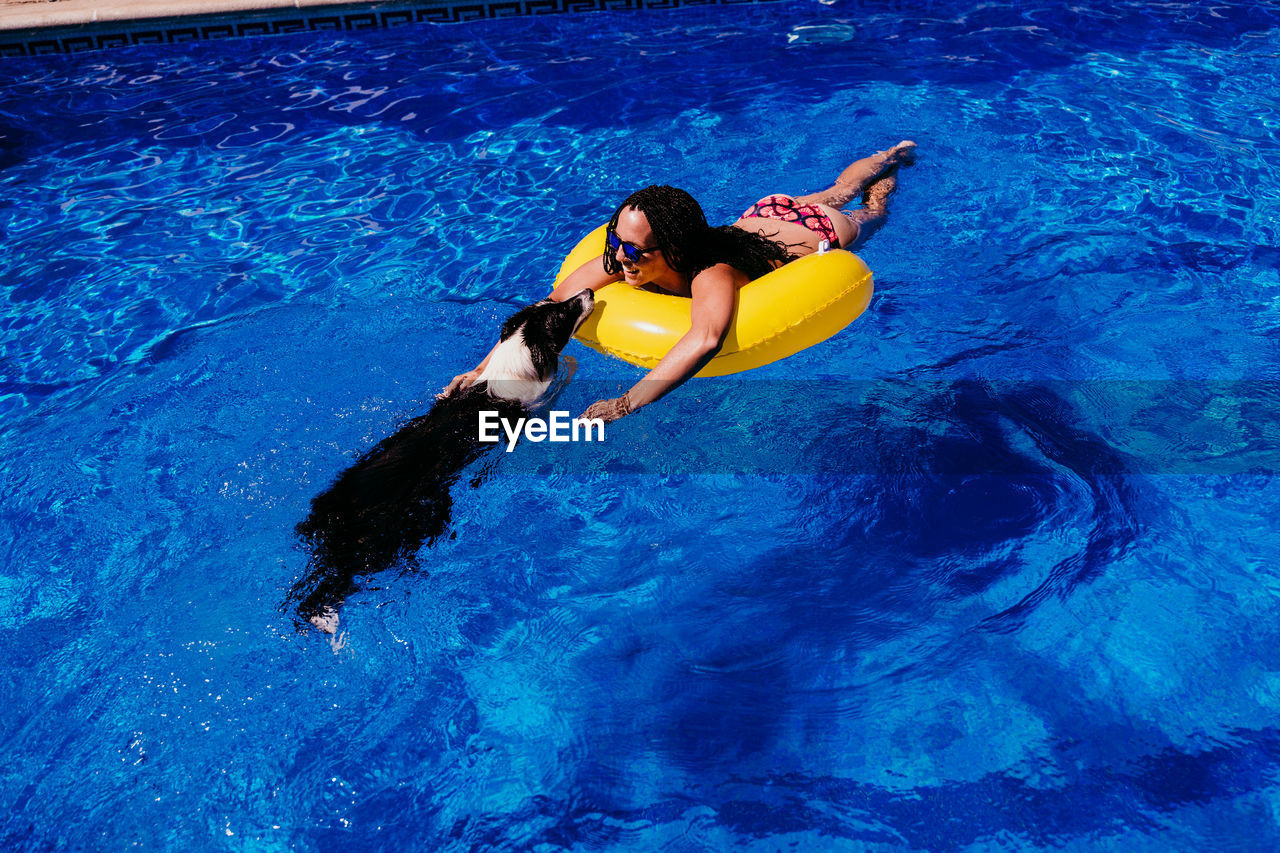 HIGH ANGLE VIEW OF WOMAN SWIMMING IN WATER