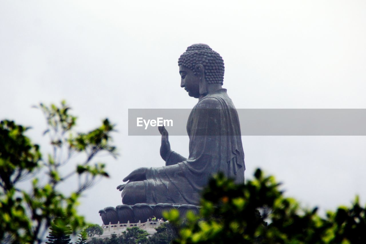 Low angle view of tian tan buddha against sky